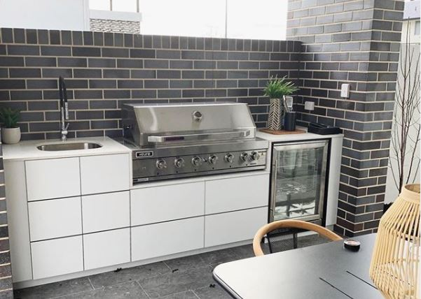 a small outdoor kitchenette with monochrome cupboards and a slightly mid-century vibe