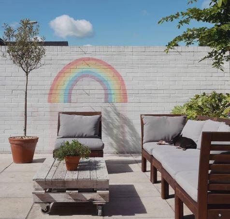 garden play area ideas with a plain grey wall painted with a chalk rainbow