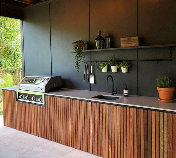 a long kitchen counter with in-built grill in an outdoor kitchen