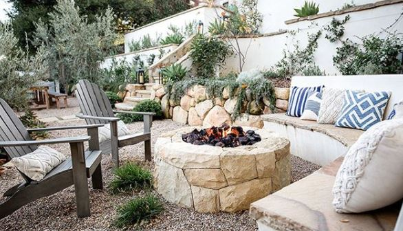 a stone fire pit with low, comfy seating around it