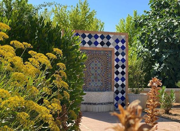 a busy garden with a tiled archway surrounding a small fountain
