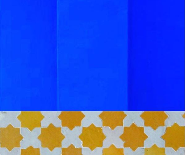 a close-up of a wall painted Majorelle blue with yellow and white tiles