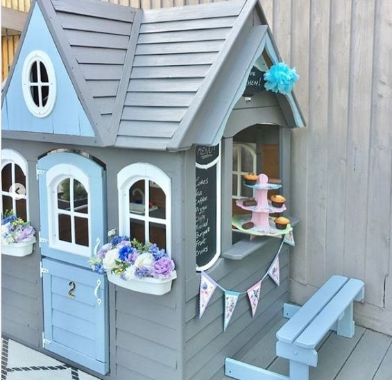 a playhouse decorated as a cake shop with muffins on the windowsill