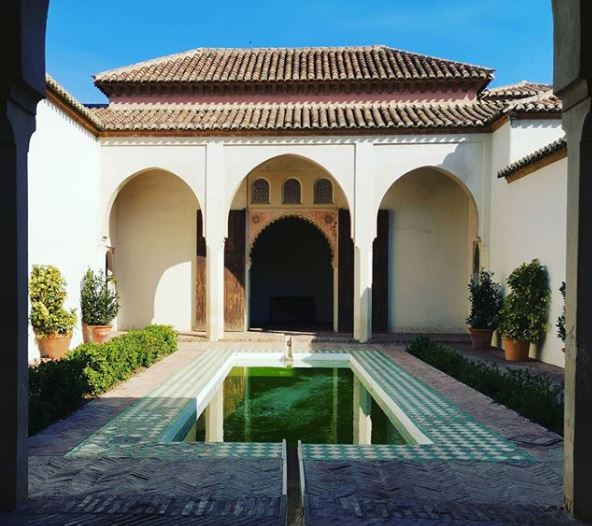 a Spanish style courtyard with a long central pool and brightly patterned tiles