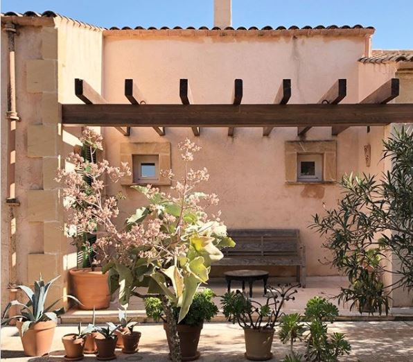 a peach stucco building with a pergola-covered patio and potted plants