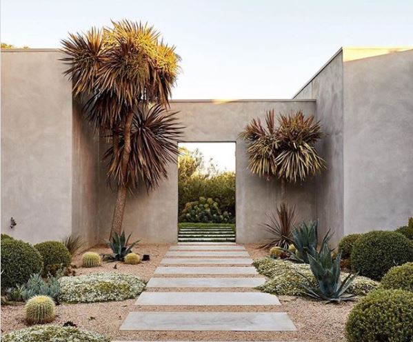 a gravel garden with drought-tolerant plants and a paved path leading through a stucco arch