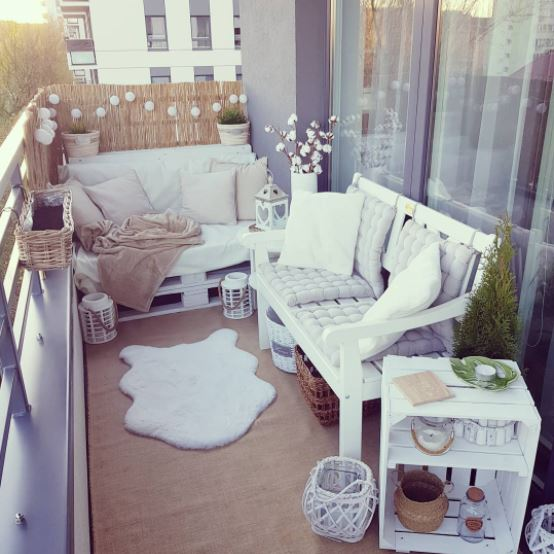 a small, cosy balcony with pallet seating and fine bamboo matting to create privacy