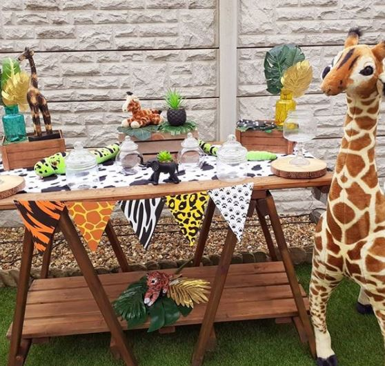 a party food table with animal-print bunting and safari decor