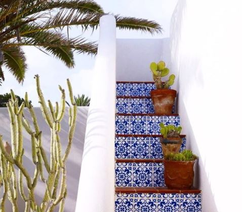 Steps on a white stucco building tiled with terracotta and bright blue patterns