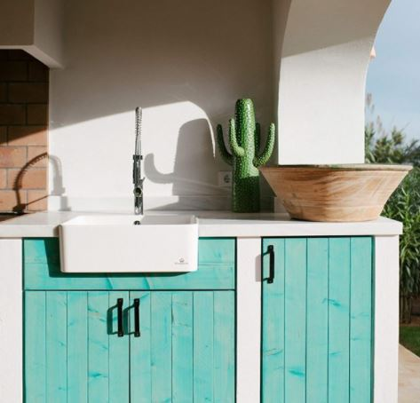 an outdoor kitchen with stucco walls and wooden cupboards stained turquoise
