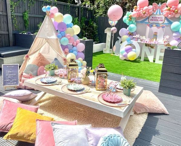 pastel coloured kids garden party ideas with balloons and floor seating