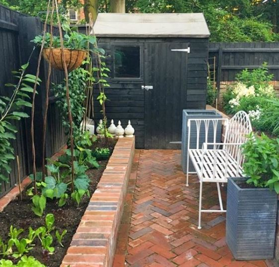 a little shed at the end of a red brick garden path with a raised vegetable patch