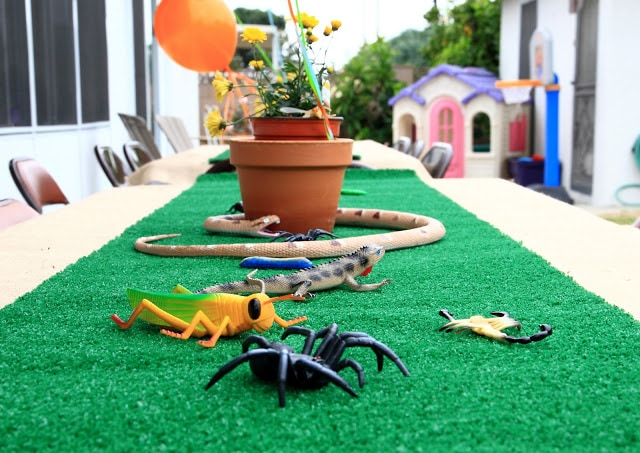 artificial grass table cloth covered with plastic bugs for a kids birthday party