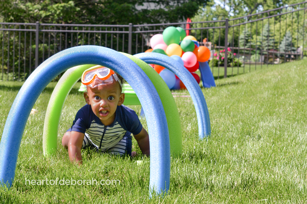 young boy crawling through pool noodle obstacles