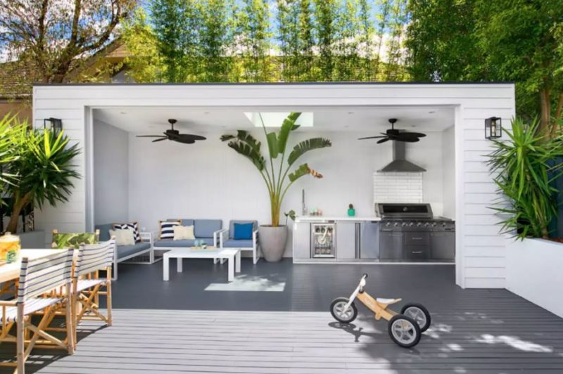 an open-fronted garden shed with outdoor kitchen inside