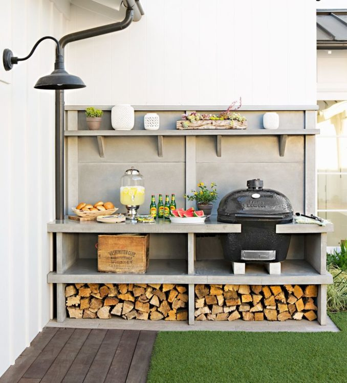 a narrow outdoor kitchen with a kamado cooker and wood store