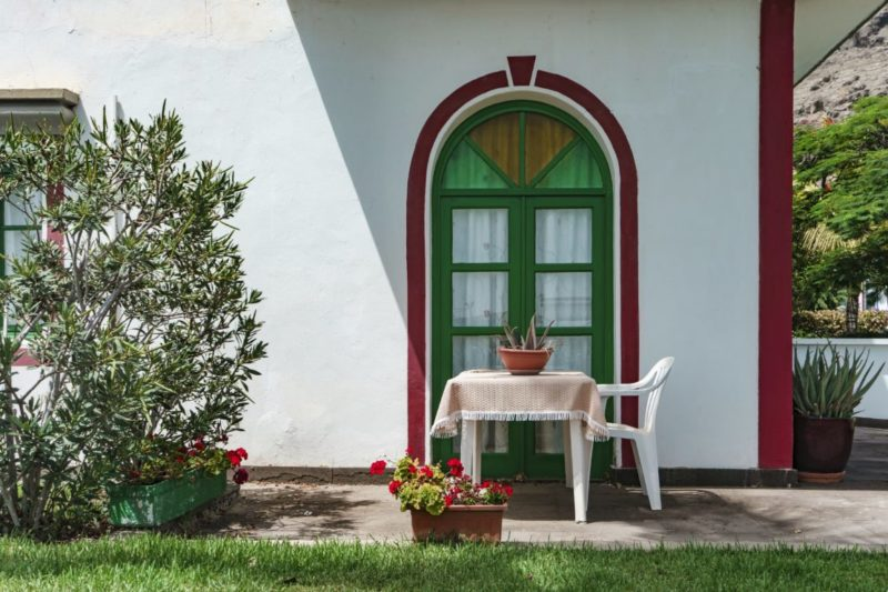 a white wall with a green door and a red archway painted around it