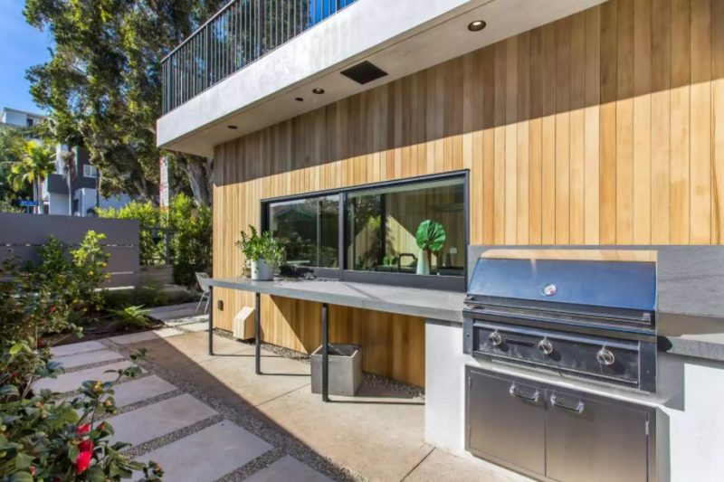 an outdoor kitchen along the exterior of a house, with a sliding window to the indoor kitchen