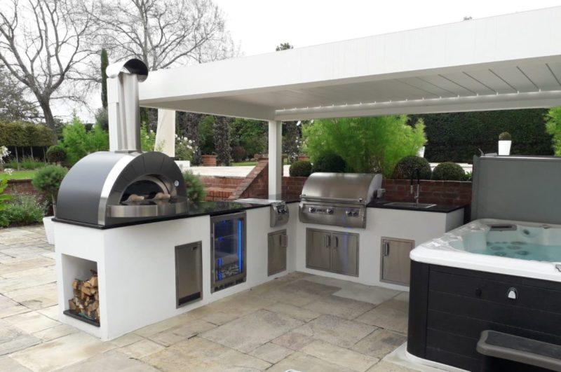 a hot tub and a luxurious garden kitchen area under a roof