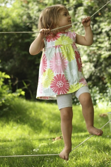 child balancing on tightrope between trees