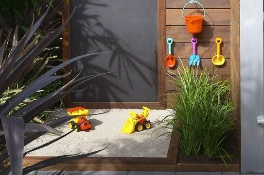 an outdoor sand pit and chalk board for children