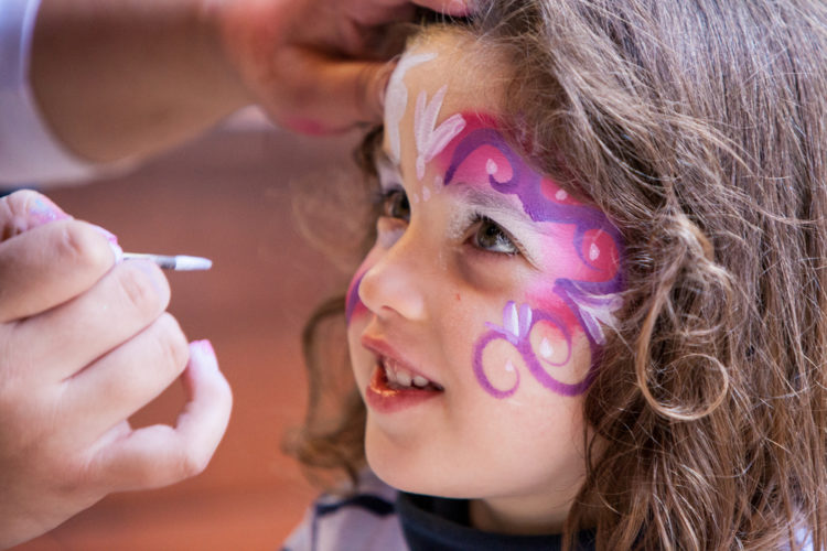 a young girl having her face painted pink