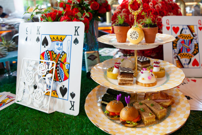 decorative playing cards and a cake stand with afternoon tea