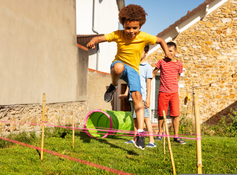 race with obstacles child jumping over hurdle