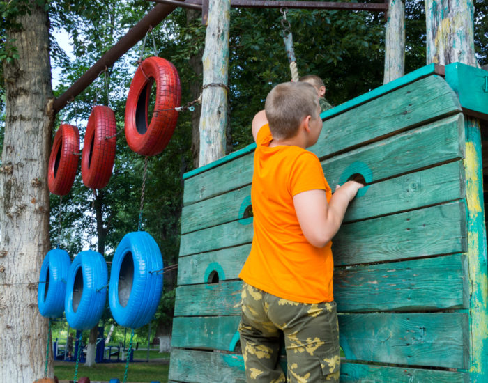 boy on a climbing wall with tyres