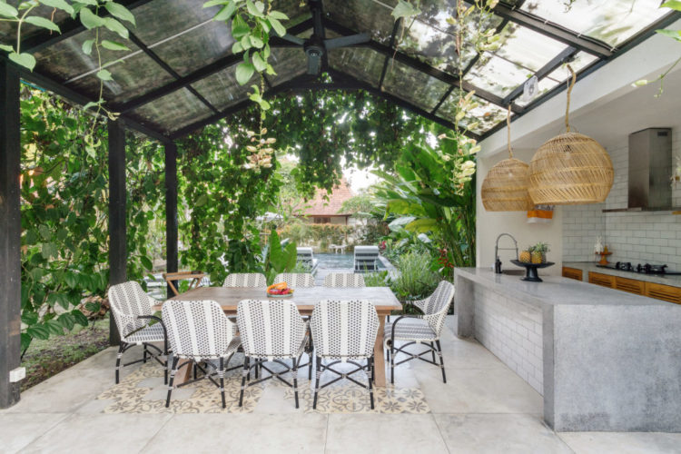 a garden kitchen and dining area covered by a metal and glass roof