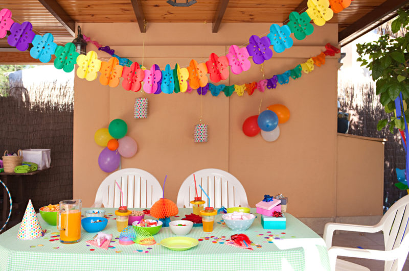 a table under a pergola covered with party decor