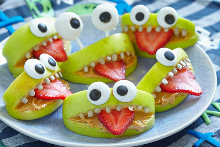 party food ideas with apple wedges made to look like cute monsters with sugar eyes and strawberry tongues