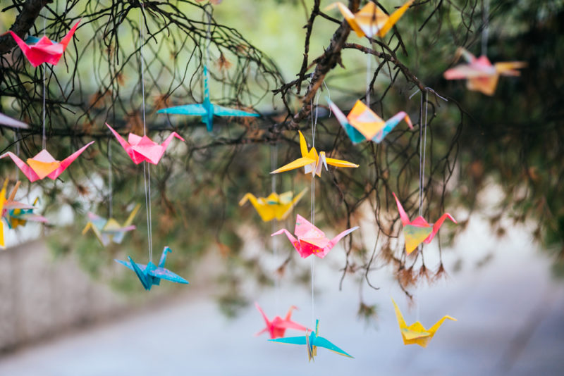 little origami paper cranes hanging from tree branches
