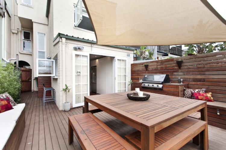 a terraced home with outdoor kitchen deck and patio seating