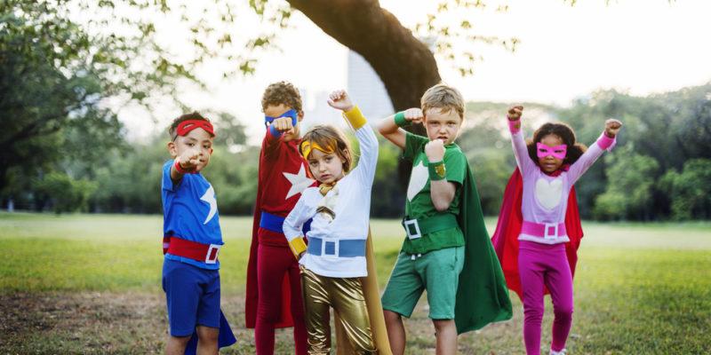 five kids playing, dressed as superheroes