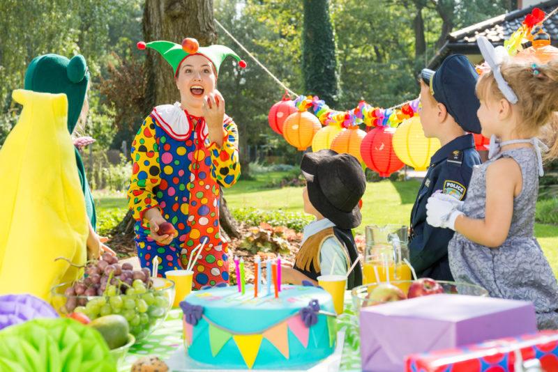 a clown juggles to entertain children in the garden