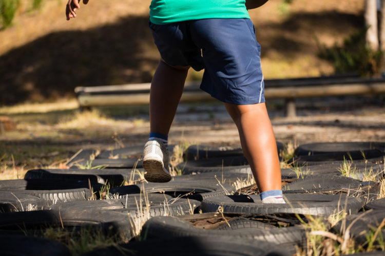 child running through tyres laid out on the ground