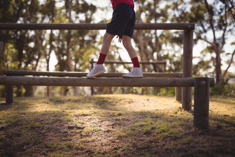 child balancing on outdoor beam