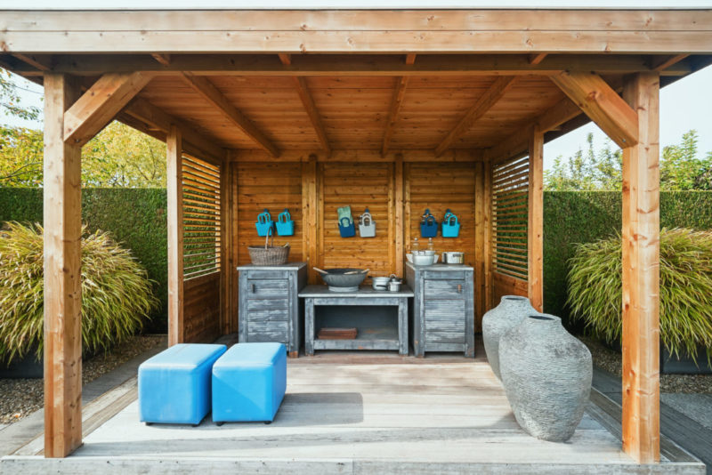 a gazebo with rustic wooden kitchen units and blue cushioned benches