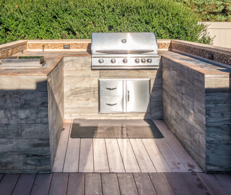 a u-shaped kitchen at the end of a contemporary garden deck