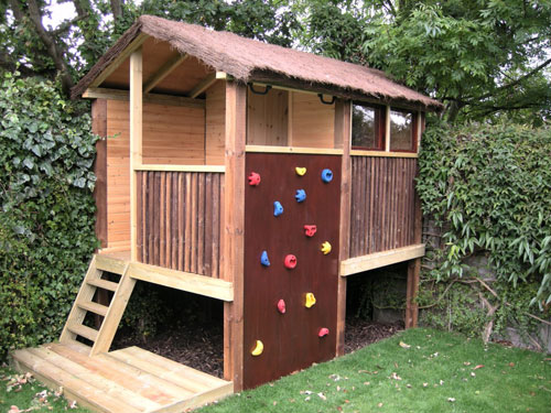 kids garden play area ideas featuring a treehouse with climbing wall