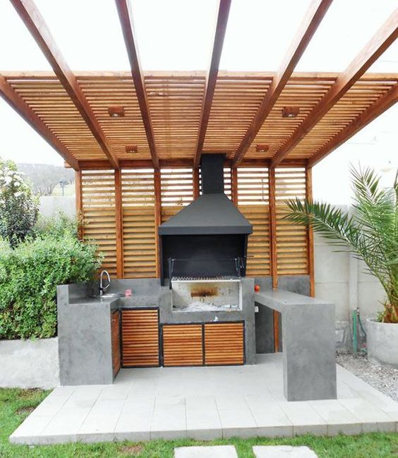 outdoor kitchen ideas using concrete for surfaces and slatted teak cupboards and pergola