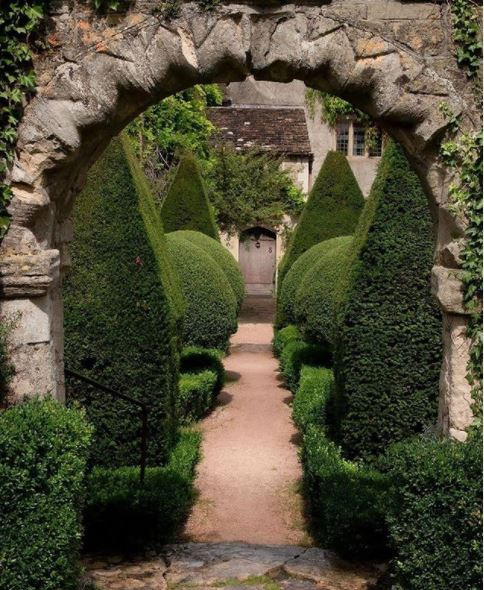 an archway with a row of elaborate topiaries behind it