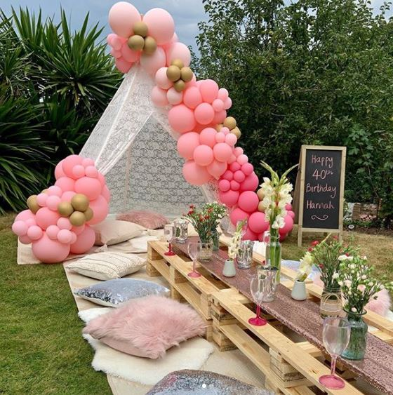 a lace tent at the head of a table, covered in balloons