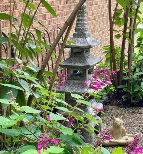a stone lantern next to a leafy flower bed