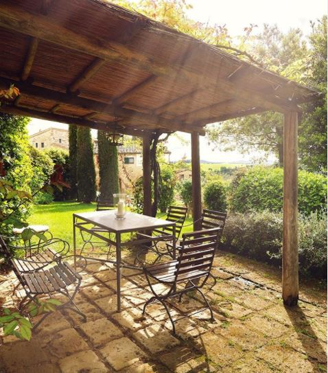 a shady pergola above a mossy patio with garden furniture