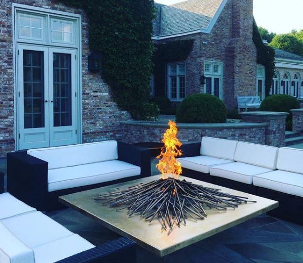 a futuristic square fire pit with stylised metal twigs
