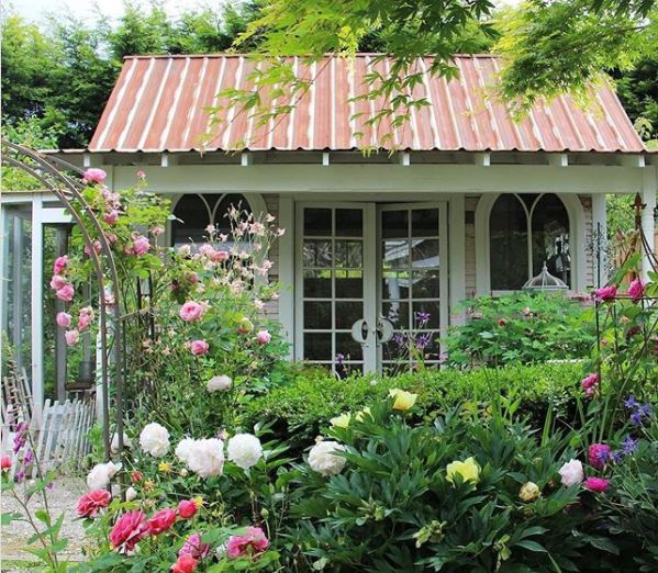 a pretty green shed with church style windows