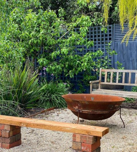 a rust coloured metal fire bowl in a simple, homely patio area
