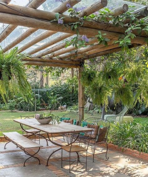 an open pergola above a patio dining set with lots of plants